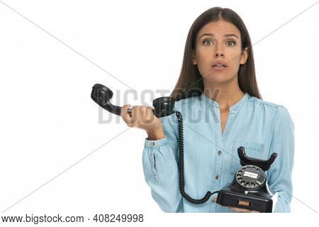 young casual woman feeling perplex over her phone conversation against white background