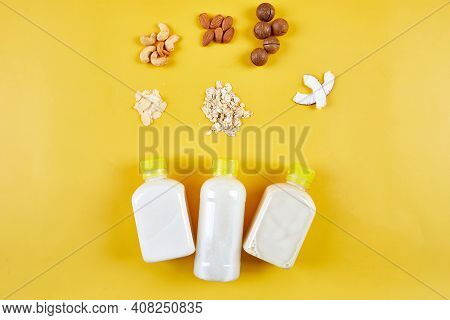 Alternative Types Of Vegan Milks In Bottles On A Yellow Background