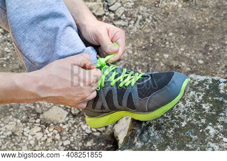 Male Hands Tying Up Shoelaces On A Running Sneaker, Close Up. Part Of Sportsman Tying Sneakers. Leg
