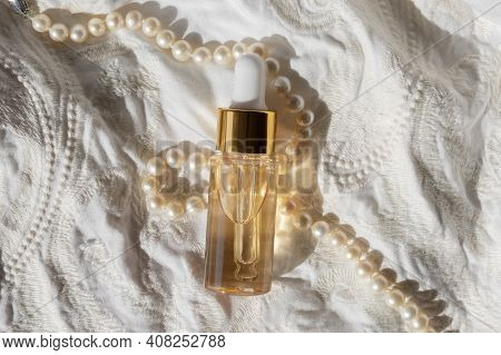 Gold Beauty Serum In A Pipette Bottle On An Ivory Fabric Regency Fashion Inspiration