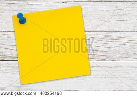 Yellow Sticky Note Paper With Pushpin On Weathered Wood With Copy Space For Your Office Message