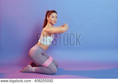 Sporty Dark Haired European Female Wearing Top And Leggins Sitting On Knees On Floor And Doing Sport