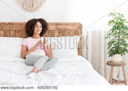 Weekend, Good Morning, Positive Mood And Vitality. Happy African American Female Sitting On Bed, Hol
