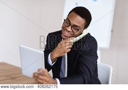 Happy Black Man In Suit Office Manager Or Businessman Talking On Phone, Using Digital Tablet At Work