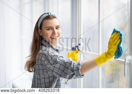 Smiling Young Woman With Detergent And Rag Cleaning Window Glass. Cheerful Millennial Lady Doing Hou