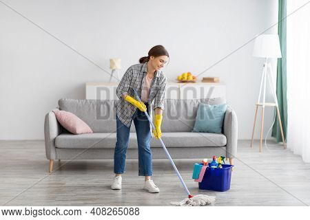 Full Length Portrait Of Happy Young Woman Wiping Floor In Living Room, Copy Space. Millennial Housew