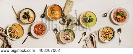 Flat-lay Of Vegetarian Creamy Homemade Soup And Spoons Over White Plain Table Background, Top View.