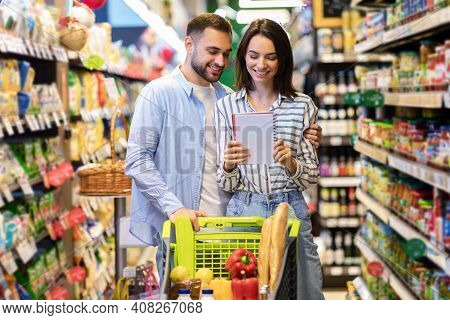 Young Lovely Couple With Shopping Cart Full Of Healthy Eco Products Looking Into Their Grocery List