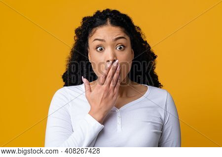 Omg. Portrait Of Shocked Black Woman Covering Mouth With Hand And Looking At Camera, Emotionally Rea