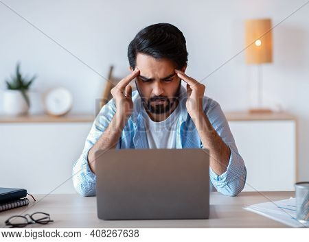 Stressed Eastern Businessman Suffering From Headache Or Business Problems At Workplace, Overworked A