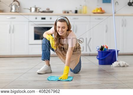 Professional Cleaning Service. Cheerful Young Lady In Apron And Rubber Gloves Washing Floor In Moder
