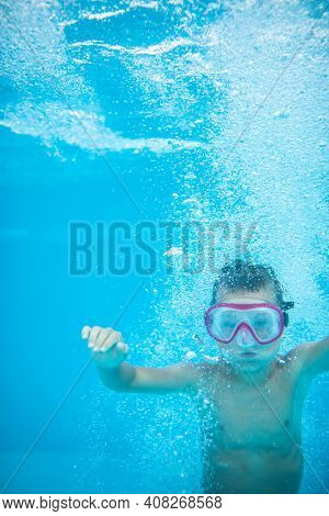 Cute little boy in a swimming pool, diving, swimming underwater, having fun