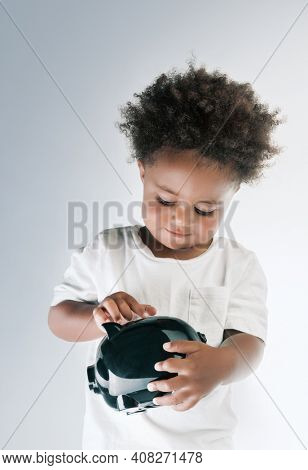 Portrait of a Nice African American Child Putting Coins in to the Pig-shaped Money Box Isolated on Grey White Background. Investment in to the Future