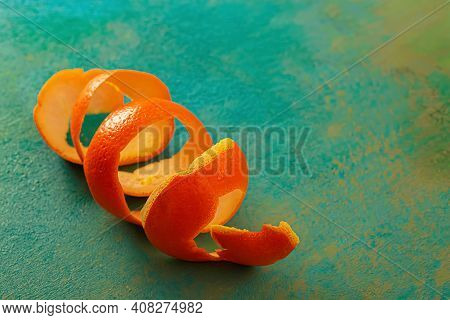 Macro Of Spiral Citrus Fruit. Background With Spiral Mandarin Peel On A Green Wooden Table. Artistic