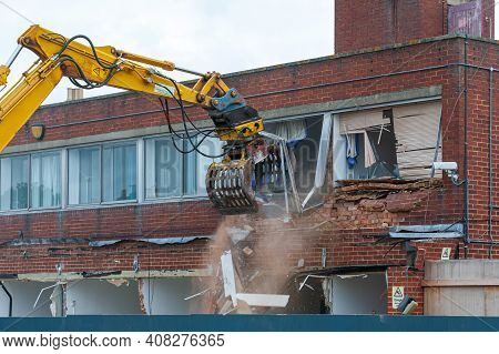 Demolition Of An Old Building With A Long Reach Machine Hydraulic Jaw. Regeneration Of A Space For N