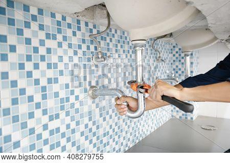 Plumber Working In The Bathroom, Plumbing Repair Service, Repairing Leaking Sinks With Adjustable Wr