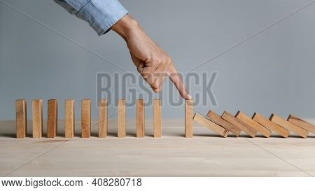 Businessman Hand Stopping The Domino Wooden Effect Concept For Planning,risk And Strategy In Busines
