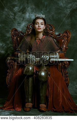 History of the Middle Ages. Full length portrait of a medieval queen in knightly armor sitting on a throne on a vintage background.
