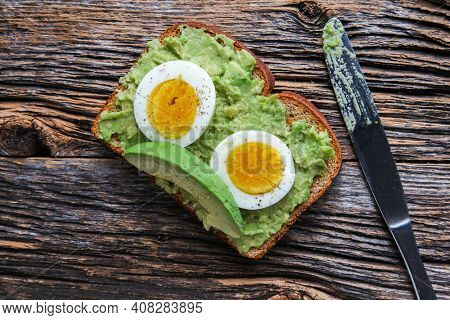 Toast with mashed avocado and eggs with knife on rustic wooden table from above