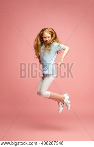 Jumping High. Happy, Smiley Redhair Girl Isolated On Pink Studio Background With Copyspace For Ad. L