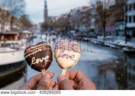 Love Romantic Ice Cream With On The Background People Ice Skating At The Frozen Canals Of Amsterdam,