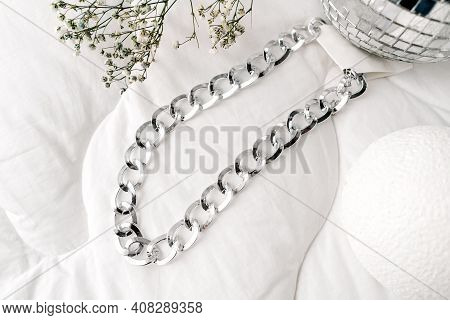 Imitation Jewelry, Silver Bijouterie Chain On White Textile Background. Dry Little Flowers Like Deco