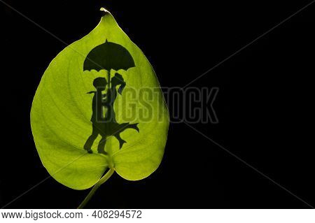 Conceptual Silhouette Of Romantic Couple Embracing Holding An Umbrella