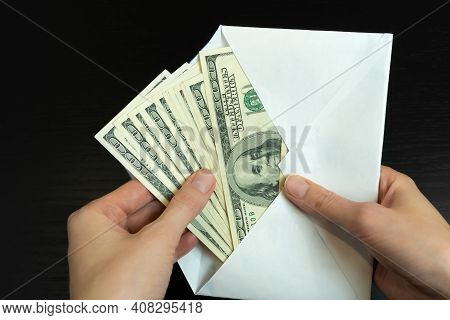 Women's Hands Take Out Dollars From A White Envelope On A Black Background Close-up. Concept Of Brib