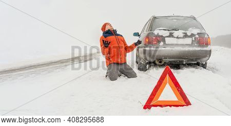 Angry Young Man In An Orange Jacket Is Kneeling On A Snow-covered Road. He Is In A State Of Stress B