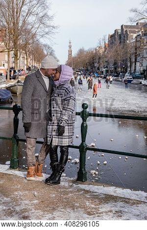 Couple Visit Amsterdam During Winter With People Ice Skating On The Canals In Amsterdam The Netherla