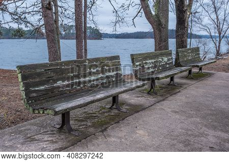 Three Sitting Benches In A Line For Viewing And Resting At The Lake By The Shoreline Along The Trail