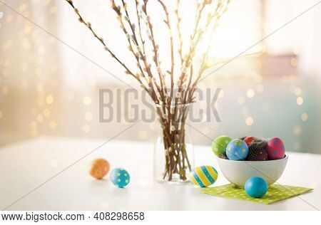 holidays and object concept - pussy willow branches and colored easter eggs in vase on table over bokeh lighs