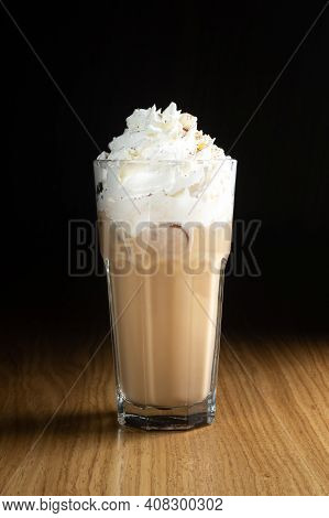 Ice Latte Macchiato Coffee With Syrup And Ice In A Transparent Glass On A Wooden Table
