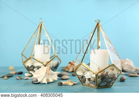 Stylish Glass Holders With Burning Candles, Seashells And Pebbles On Light Blue Wooden Table