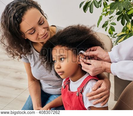 Cute Girl With Her Mother During Install Hearing Aid By Her Audiologist. Hearing Treatment For A Chi