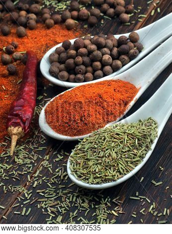 Traditional Spices. Chili Peppers, Rosemary And Allspice In Spoons On The Table
