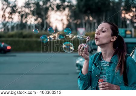 Beautiful Woman Blowing Soap Bubbles Outdoors. Young Beautiful Hipster Girl Bubble Blower In The Cit
