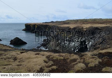 Lava Rock Cliffs And Basalt Columns On The Coast Of Iceland.