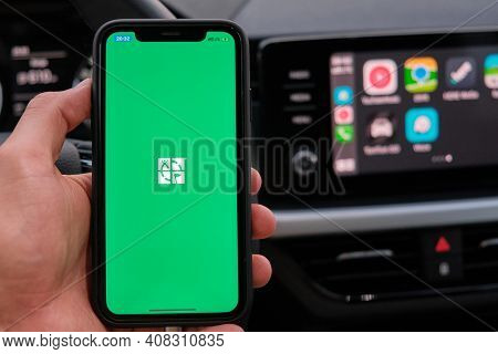Xxx On The Screen Of Smart Phone In Mans Hand On The Background Of Car Dashboard Screen With Applica