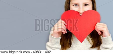 Close-up Portrait Of Young Teen Girl Holding In Hands Big Large Paper Heart Isolated On Gray Backgro