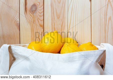 Eco Fiber Bag Full Of Fresh Whole Lemons Near Wooden Wall Close-up. Healthy Natural Food For Detox A