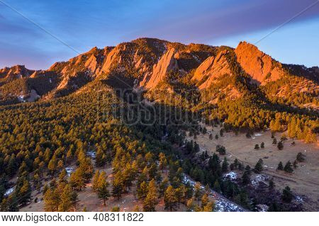 Aerial photo just after sunrise on Green Mountain with the Flatirons illuminated above Boulder, Colorado in winter.