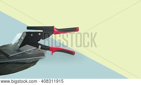 New Professional Tool,slate Cutter,black With Red Handles,isolated On Blue-green Background,sheets O