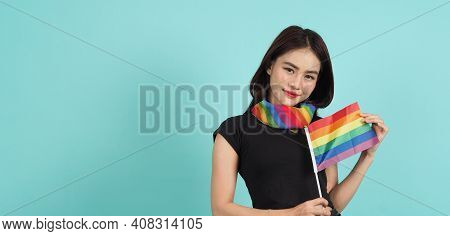 Portrait Of Young Girl Holding An Lgbt Flag Standing Against A Blue Green Background Studio.