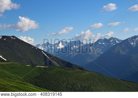 Alpine Valley With Green Slopes In The Foreground And Against The Background Of A Rocky Ridge With S
