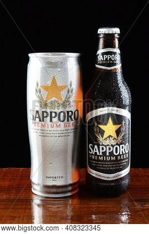 IRVINE, CA - JUNE 18, 2015: A can and bottle of Sapporo Beer on a wet bar. The Japanese brewery founded in 1876 by German trained brewer Seibei Nakagawa is the oldest beer brand in Japan.