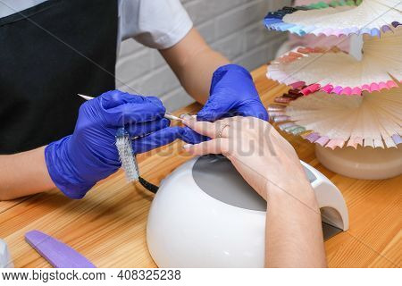 Nail Care. A Manicure Master Makes A Manicure. Beauty Saloon. The Manicurist Covers The Nails With V