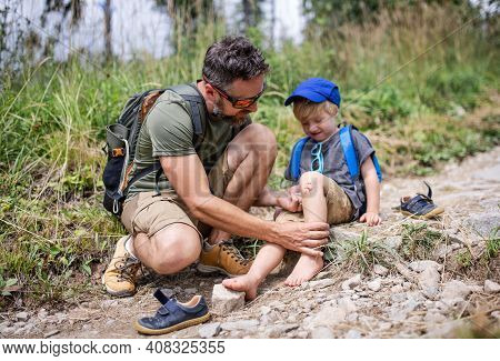 Father With Small Son On Trek Outdoors In Summer Nature, Falling And Scratched Knee Concept.