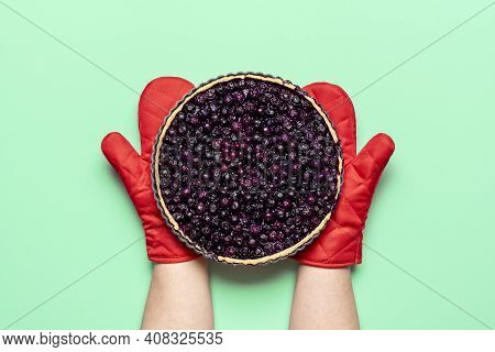 Homemade Blueberry Pie, Freshly Baked, Held In Hands With Oven Mitts, Isolated On Green Colored Back
