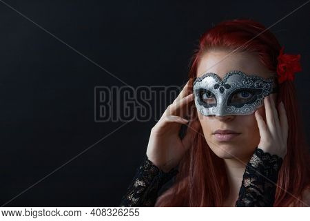 Low Key Portrait Of Redhead Young Woman Holding Silver Carnival Mask On Her Face. Horizontally.